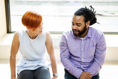 Photo for Redhaired young woman and black guy talking - Royalty Free Image