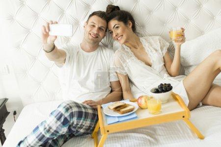 Photo pour Beau sourire jeune couple collant à chaque othe rand faire selfie tout en étant couché dans le lit - image libre de droit