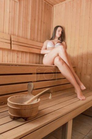 Photo pour Jeune femme de se détendre dans le sauna - image libre de droit