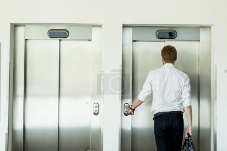 Young businessman in front of  elevator...
