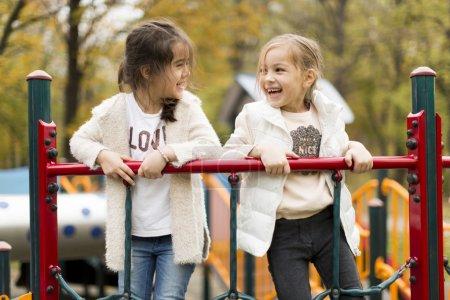 Photo pour Petites filles mignonnes sur l'aire de jeux - image libre de droit