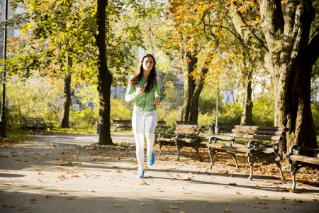 Photo for Young woman running in the park - Royalty Free Image