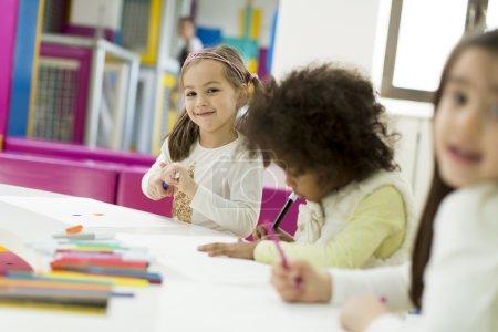Photo pour Enfants multiraciaux dessinant dans la salle de jeux - image libre de droit