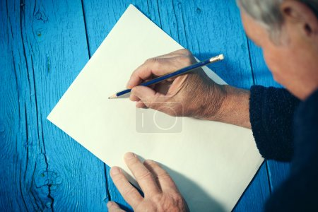 Senior man with blank white paper sheet and pencil