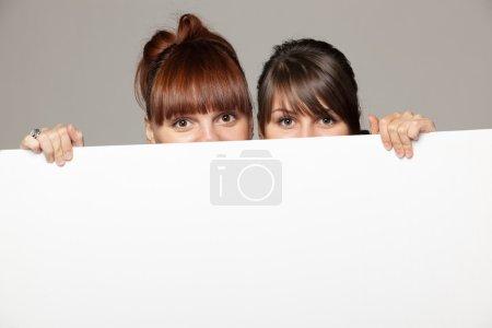 Two young women peeking over edge of blank empty paper billboard