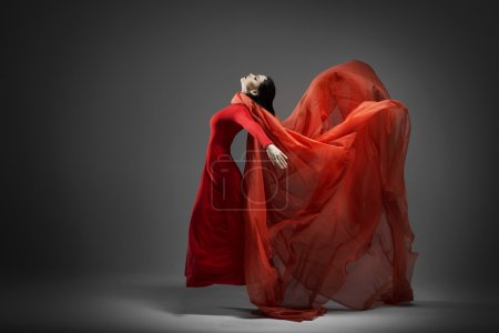 Photo for Woman in red dress dancing with flying fabric - Royalty Free Image