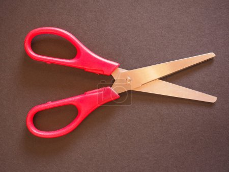 Red scissors with cutting lame open over black bac...