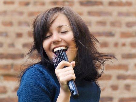 Girl sing into hair brush