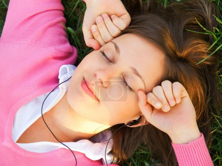 Photo for Woman listening to music in headphones laying on the grass - Royalty Free Image