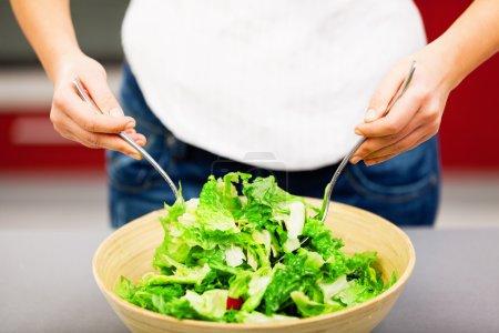 Photo pour Jeune femme faisant salade dans la cuisine - image libre de droit