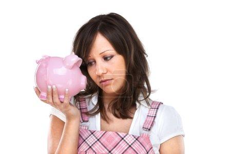 Photo pour Young woman with a sad expression holding pink pig money-box - Piggy Bank - image libre de droit