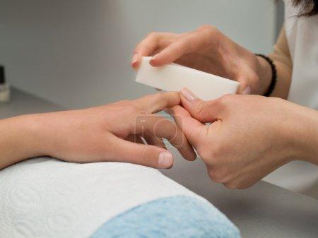 Girl's fingernails being manicured