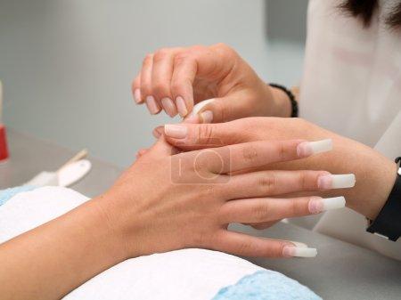 Girl fingernails being manicured.