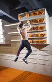 Young man practicing rock-climbing in climbing gym