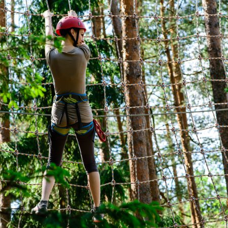 Young woman climbing in adventure park
