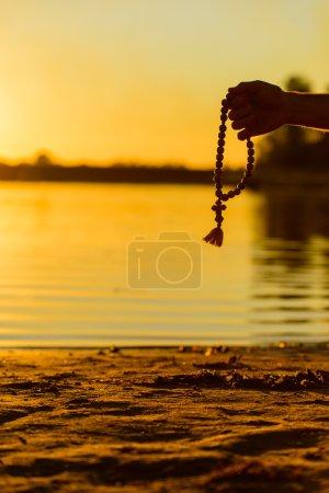 Photo pour Silhouette du chapelet dans les mains des hommes sur le fond de la plage et le coucher du soleil - image libre de droit