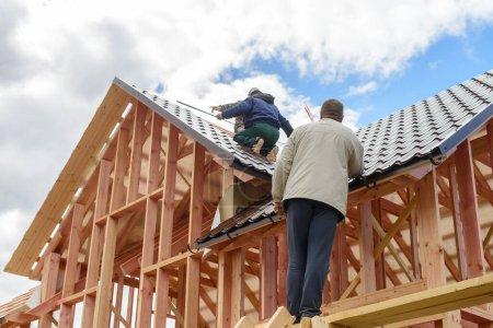 Photo pour Maître constructeur faire le toit de la maison à ossature, métal sur le toit de la maison neuve. Construction de toit. Construction en bois - image libre de droit
