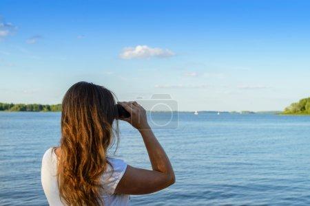 Mujer mirando a través de los prismáticos como un futuro brillante, aterriza