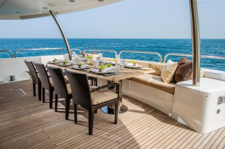 Photo for Dinning table on the upper deck in luxurious yacht with open sea view. - Royalty Free Image