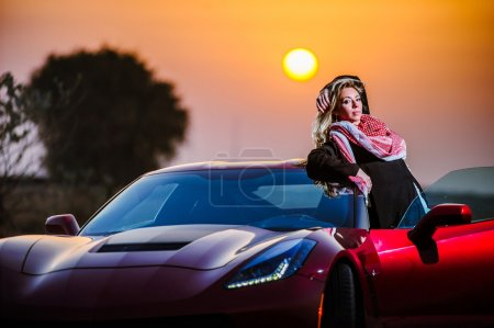 Arabic way dressed yang woman posing in red car in desert.