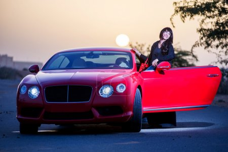 Arabic way dressed yang woman posing in red car in desert.