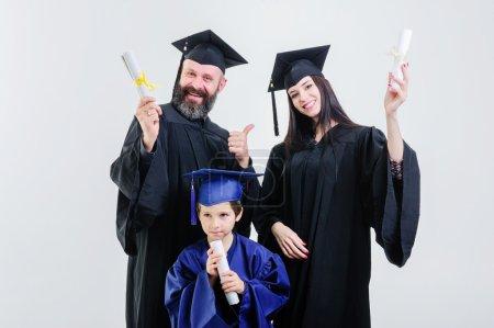 Photo pour Collège de trois succès différents âge diplômés, portant casquette et robe, titulaire de diplôme sur le fond gris. - image libre de droit