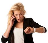 Mladá blondýnka se dívá na hodinky, když byla pozdní iso