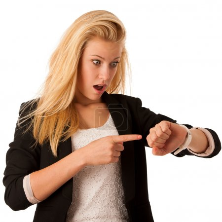 Young blonde woman looks at her watch when she is being late iso