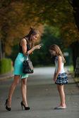 Matka mluví na zlobivé děvče na ulici, v parku