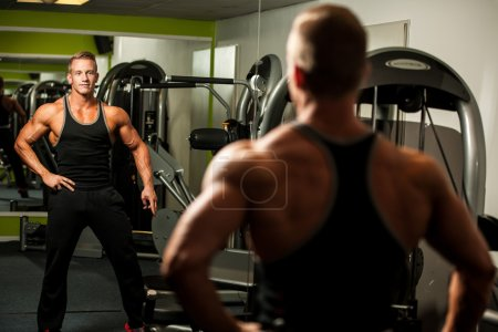 Handsome man looking in mirror after body building workout in fi