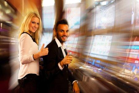 young couple winning on slot machine in casino