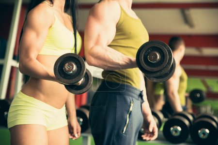 Fitness couple working out in gym with dumbbells