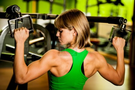 beautiful muscular fit woman exercising building muscles in fitn