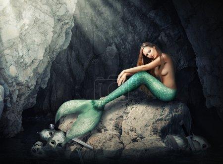 Beautiful woman mermaid sitting  in cave.