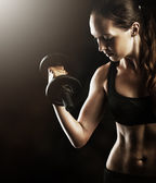 fitness muscular woman working out with dumbbells