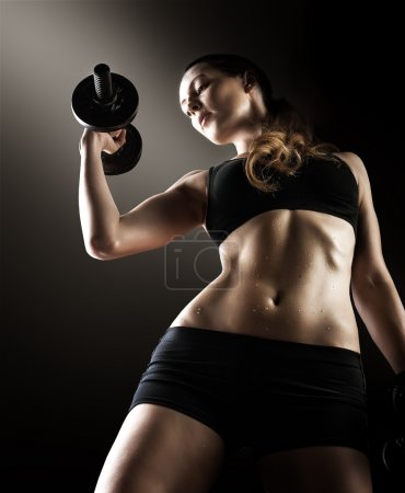 Dark contrast photo of young beautiful fitness woman