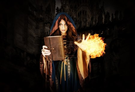 halloween witch holding magical book of spells making magic