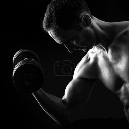 Silhouette of young muscular fitness man on black