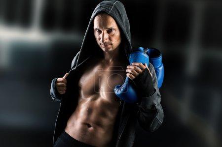 Dangerous  muscular man boxer wearing jacket with hood