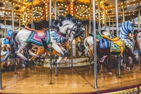 Old French carousel in a holiday park. Three horses and airplane