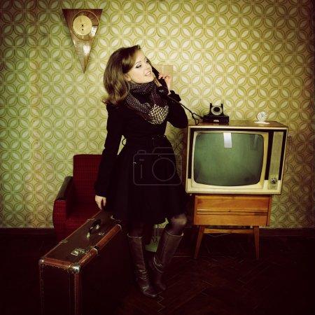 Photo pour Portrait d'art de jeune femme debout en appelant téléphone dans la chambre avec le papier peint et l'intérieur avec tv, horloges, chaise et valise, stylisation rétro des années 60-70, tonique - image libre de droit
