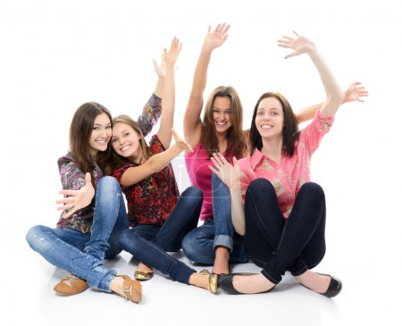 Photo for Happy teen girls sitting together and smiling with hand up over white - Royalty Free Image