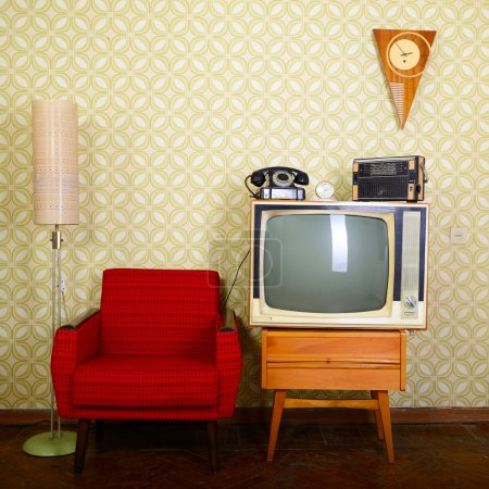 Photo for Vintage room with wallpaper, old fashioned armchair, retro tv, phone, clocks, radio player and standart lamp - Royalty Free Image