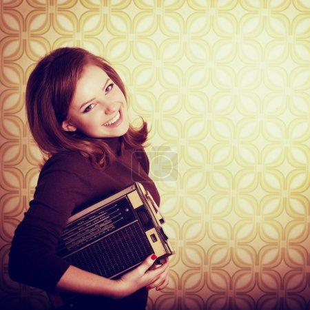 Foto de Arte retrato de sonriente extática joven sosteniendo reproductor de radio en cuarto con papel pintado vintage, retro estilización 60-70s, entonado - Imagen libre de derechos