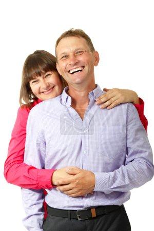Photo pour Jolie femme joyeuse avec l'homme amoureux souriant sur fond blanc. Portrait de femme mûre heureuse étreint son mari, isolé - image libre de droit