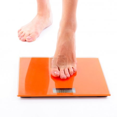 Woman steps on scales.