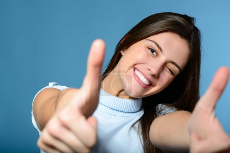 Photo for Portrait of a beautiful, confident and cheerful teenager girl showing thumbs up isolated on blue - Royalty Free Image
