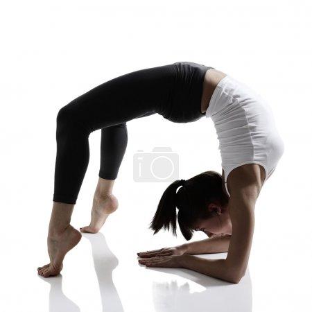 Photo pour Portrait de fille de sport faisant du yoga exercice d'étirement, studio tourné dans la technique de la silhouette sur fond blanc - image libre de droit