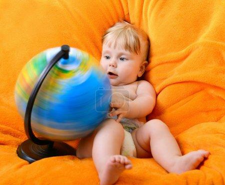 Photo pour Heureux souriant petit garçon jouant avec globe terrestre, assis sur un fauteuil mou orange - image libre de droit
