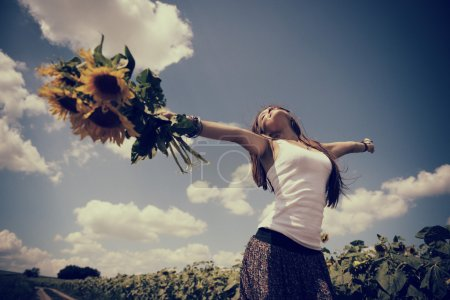 Photo for Young beautiful woman enjoying summer, youth and freedom, holding sunflowers above head against blue sky - Royalty Free Image